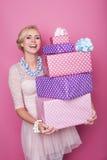 Mujer rubia de risa que sostiene las cajas de regalo coloridas grandes y pequeñas Colores suaves La Navidad, cumpleaños, día de S Fotos de archivo
