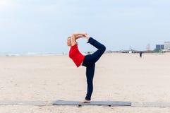 Mujer rubia del ajuste deportivo en ropa de deportes roja y azul marino que se resuelve al aire libre el día de verano, haciendo  Fotos de archivo libres de regalías