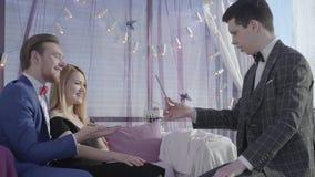 Mujer rubia del control barbudo feliz joven del hombre en los trucos mágicos de la demostración masculina del sofá y del mago par almacen de video