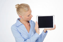 Mujer rubia del negocio que mira la pantalla de la tableta Foto de archivo