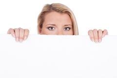 Mujer rubia detrás de la tarjeta blanca Foto de archivo libre de regalías