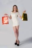 Mujer rubia divertida con los bolsos de compras Foto de archivo