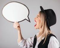 Mujer rubia divertida de griterío de la sensación de la histeria en el sombrero negro que lleva a cabo discurso buble fotos de archivo libres de regalías