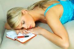 Mujer rubia durmiente con la agenda Foto de archivo libre de regalías