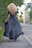 Mujer rubia elegante hermosa en el vestido de seda largo maxi negro, saliendo, al aire libre, detrás Foto de archivo libre de regalías