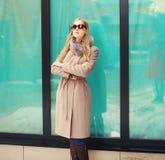 Mujer rubia elegante hermosa que lleva una chaqueta y las gafas de sol de la capa imagen de archivo