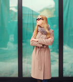 Mujer rubia elegante hermosa que lleva una chaqueta y las gafas de sol de la capa en ciudad Imágenes de archivo libres de regalías
