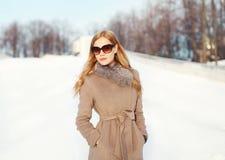 Mujer rubia elegante hermosa que lleva una chaqueta y las gafas de sol de la capa en invierno Foto de archivo