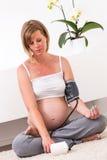 Mujer rubia embarazada en el hogar moderno Foto de archivo libre de regalías