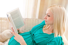 Mujer rubia embarazada que se relaja en el sofá, libro de lectura, soñando, Imagenes de archivo