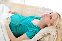Mujer rubia embarazada que se relaja en el sofá, libro de lectura, soñando, Fotos de archivo libres de regalías