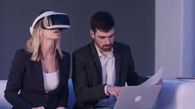 Mujer rubia en auriculares del vr que discute proyecto de construcción con su socio que sostiene modelos delante del ordenador po Imágenes de archivo libres de regalías