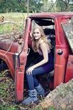 Mujer rubia en carro viejo foto de archivo