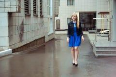 Mujer rubia en chaqueta azul del vestido y del dril de algodón que camina abajo de la calle de la ciudad contra fondo de la arqui Fotos de archivo libres de regalías