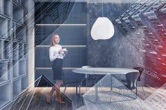 Mujer rubia en comedor del muro de cemento foto de archivo