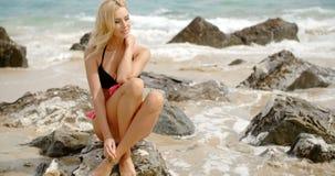 Mujer rubia en el bikini que se sienta en rocas de la playa