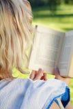 Mujer rubia en el parque que lee un libro Imagen de archivo libre de regalías