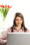 Mujer rubia en el sofá con el ordenador portátil Fotos de archivo