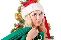 Mujer rubia en el sombrero de santa con el bolso del regalo Imágenes de archivo libres de regalías
