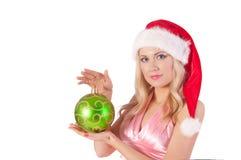 Mujer rubia en el sombrero de santa con la bola de la Navidad Foto de archivo libre de regalías