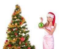 Mujer rubia en el sombrero de santa con la bola de la Navidad Fotografía de archivo