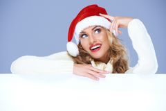 Mujer rubia en el sombrero de Santa que se reclina sobre la tarjeta blanca Fotografía de archivo