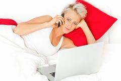 Mujer rubia en el teléfono con un ordenador portátil en una cama Fotografía de archivo