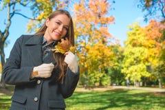Mujer rubia en Gray Coat Holding Dry Leaves Imagen de archivo