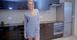 Mujer rubia en Gray Dress Standing en la cocina almacen de metraje de vídeo