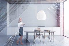 Mujer rubia en la cocina blanca con la tabla foto de archivo libre de regalías