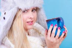 Mujer rubia en la consumición peluda del sombrero del invierno Imagenes de archivo