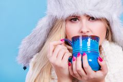 Mujer rubia en la consumición peluda del sombrero del invierno Fotos de archivo
