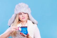 Mujer rubia en la consumición peluda del sombrero del invierno Foto de archivo