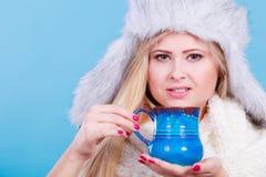 Mujer rubia en la consumición peluda del sombrero del invierno Foto de archivo libre de regalías
