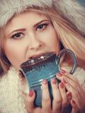 Mujer rubia en la consumición peluda del sombrero del invierno Imágenes de archivo libres de regalías