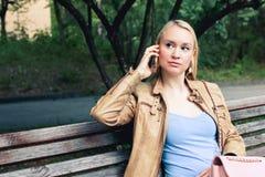 Mujer rubia en la ropa casual tolking en el teléfono con una cara seria imagen de archivo
