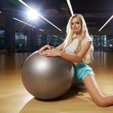 Mujer rubia en la ropa de los deportes que presenta con la bola de plata de la yoga imagen de archivo