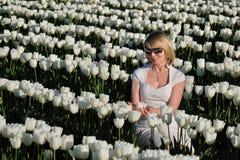 Mujer rubia en las flores blancas Foto de archivo