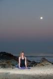 Mujer rubia en las medias del modelo que realizan la extensión trasera en la noche Fotos de archivo