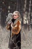 Mujer rubia en otoño en abrigo de pieles con la primera nieve del búho a mano B Fotografía de archivo libre de regalías