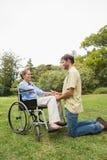 Mujer rubia en silla de ruedas con el socio que se arrodilla al lado de ella Fotos de archivo