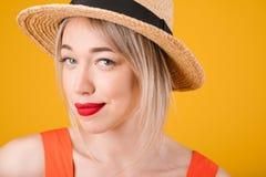 Mujer rubia en sombrero vistazo difícil Colores amarillos calientes brillantes Foto de archivo libre de regalías
