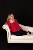 Mujer rubia en un sofá blanco Imágenes de archivo libres de regalías