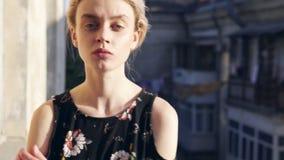 Mujer rubia en un vestido con las flores en el fondo de las calles almacen de metraje de vídeo