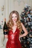 Mujer rubia en vestido rojo con la botella de vino blanco o de champán en interior de lujo Árbol de navidad, presentes y regalo Fotos de archivo