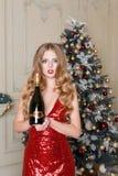 Mujer rubia en vestido rojo con la botella de vino blanco o de champán en interior de lujo Árbol de navidad, presentes y regalo Imagen de archivo