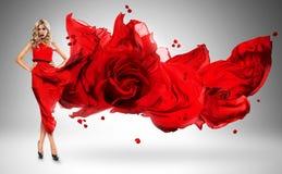 Mujer rubia en vestido ventoso de la rosa del rojo Foto de archivo libre de regalías