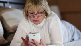 Mujer rubia en vidrios con el smartphone blanco que miente en la cama almacen de metraje de vídeo