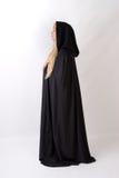 Mujer rubia en vista lateral negra del capote encapuchado Fotografía de archivo