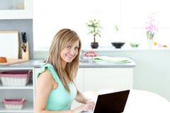 Mujer rubia encantada que usa su computadora portátil y sonrisa Fotografía de archivo libre de regalías